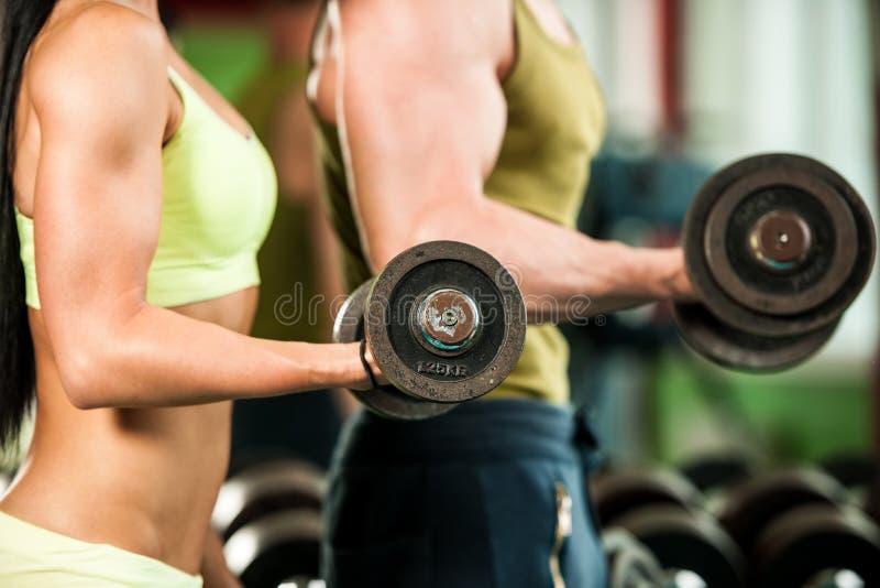 Allenamento del youple di forma fisica - MANN e la donna adatti si preparano in palestra immagine stock