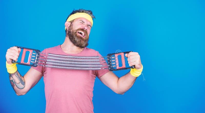 Allenamento dell'atleta con l'estensore Migliori i vostri muscoli con l'attrezzatura di sport Esercitazione barbuta dell'uomo con fotografia stock