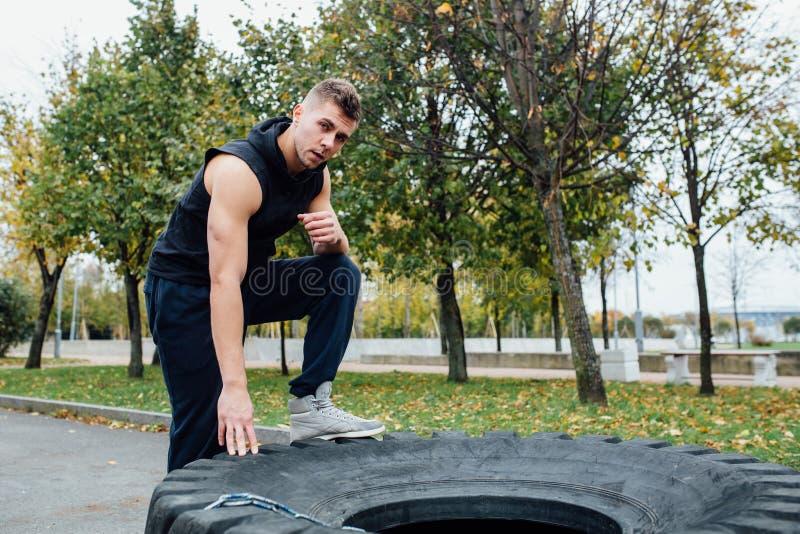 Allenamento dell'uomo di sport di forma fisica all'aperto con la gomma del trattore fotografia stock