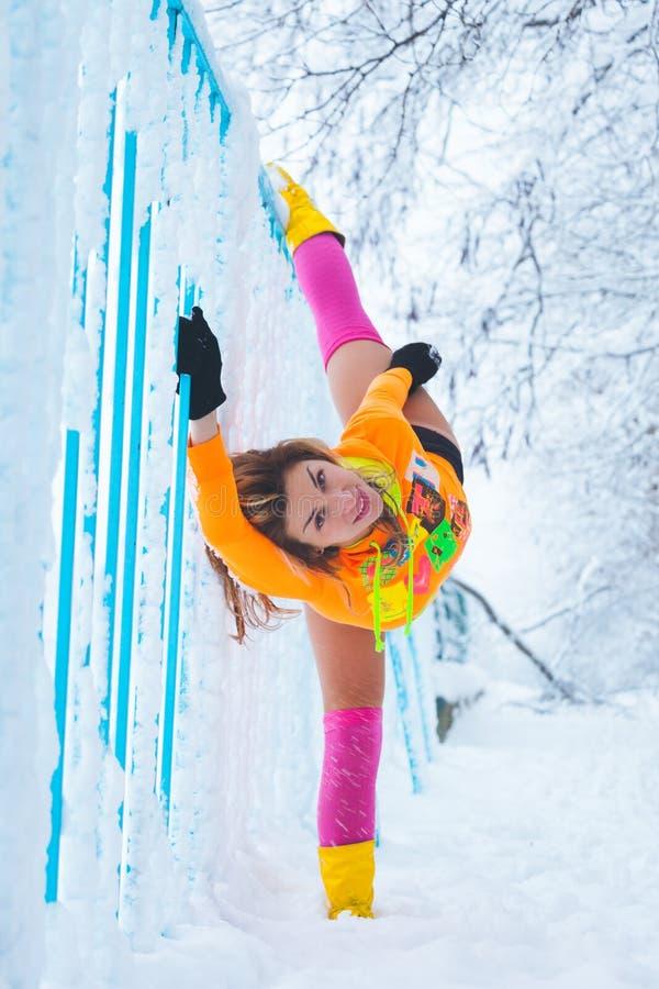 Allenamento della donna all'aperto in neve entro il giorno di inverno del recinto del metallo fotografia stock libera da diritti