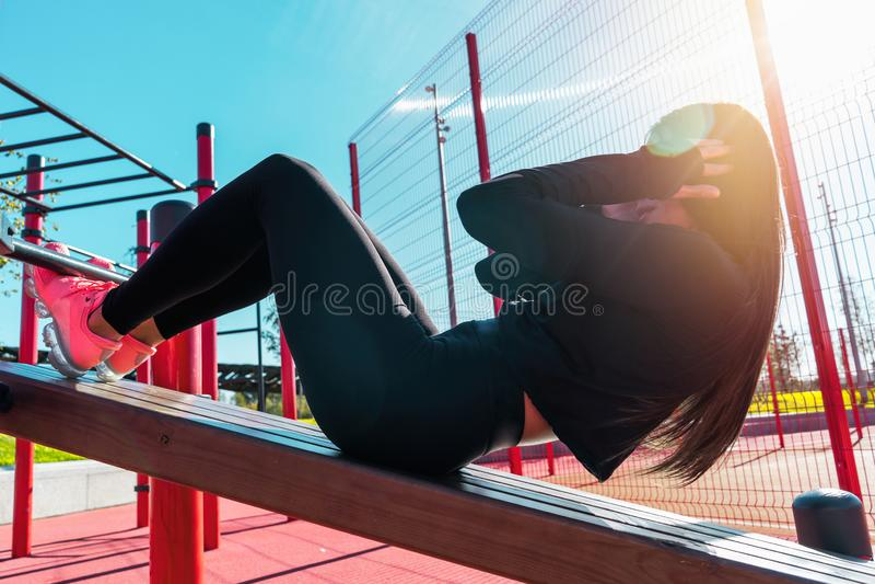 Allenamento di pratica dell'ABS della donna ed esercitarsi all'aperto nell'ambiente urbano fotografia stock libera da diritti