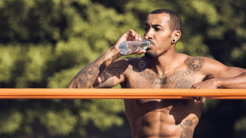Allenamento di Relaxing After Intense dell'atleta di afro, acqua potabile fotografie stock