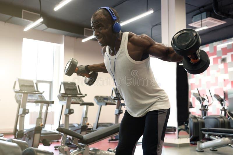Allenamento duro Uomo di colore muscolare che fa gli esercizi con le teste di legno alla palestra fotografia stock libera da diritti
