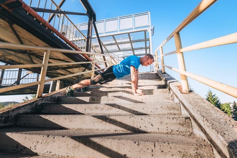 Allenamento esterno L'uomo fa per spingere verso l'alto sulle scale immagini stock