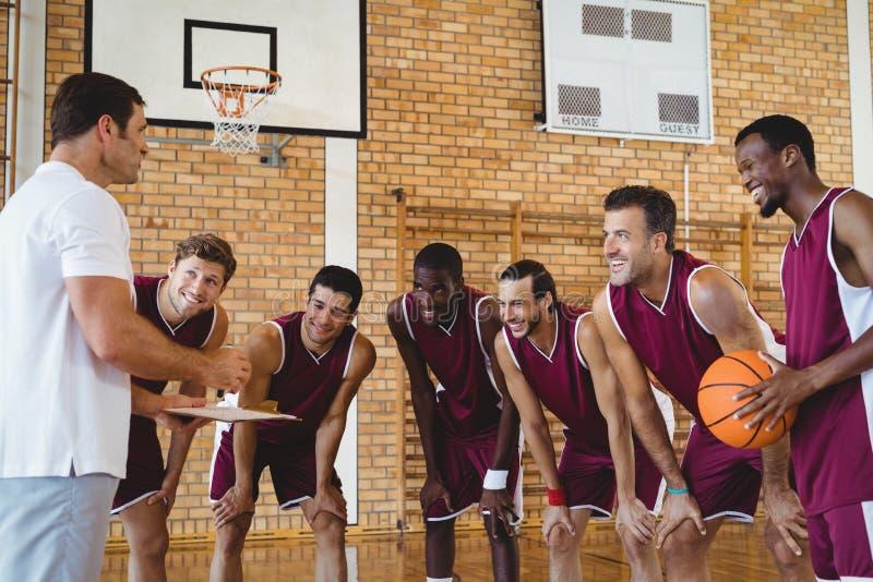 Allenatore sorridente che spiega piano tattico ai giocatori di pallacanestro fotografia stock libera da diritti