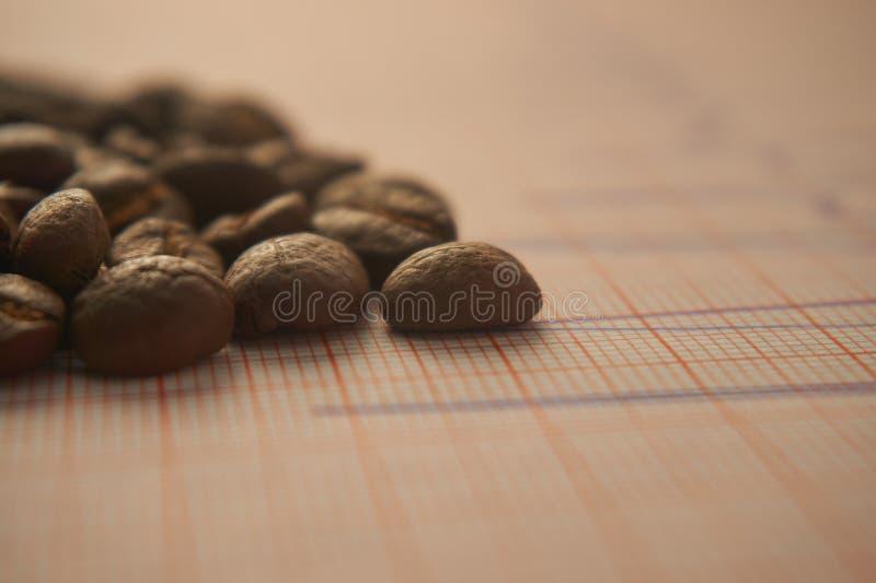Allenti i chicchi di caffè arrostiti su un tracciato di ECG fotografia stock libera da diritti