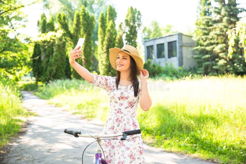 Aller à vélo assez jeune et selfie heureux de fille sur le parc d'été Heureux détendez le temps dans la ville Belle femme, jour e photos libres de droits