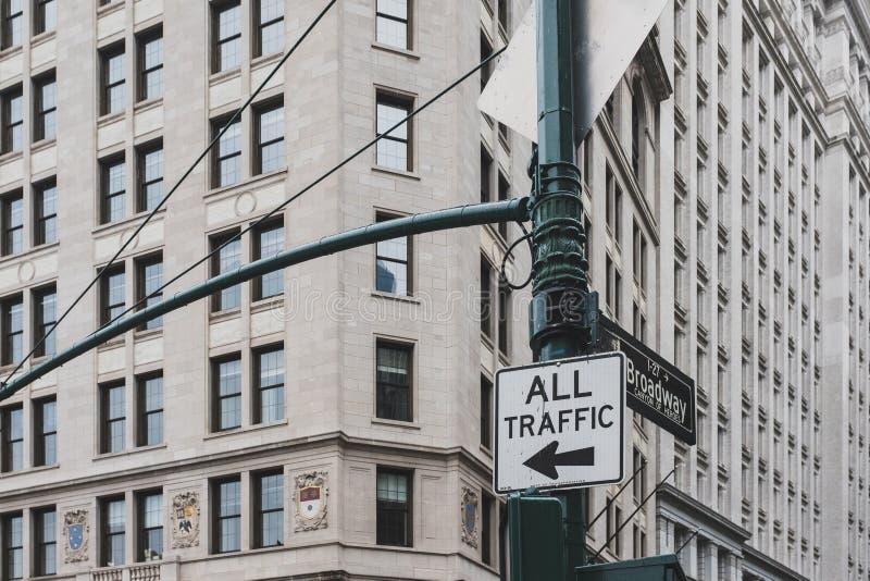 Aller Verkehr zum linken Zeichen- und Broadway-Straßennamenzeichen auf einem Straßenlaternenpfahl, gegen Äußeres des Gebäudes in  lizenzfreie stockbilder