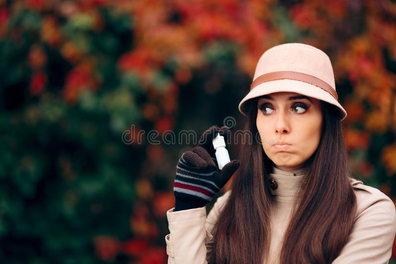 Woman with Nasal Spray Fighting Cold in Autumn Season royalty free stock images