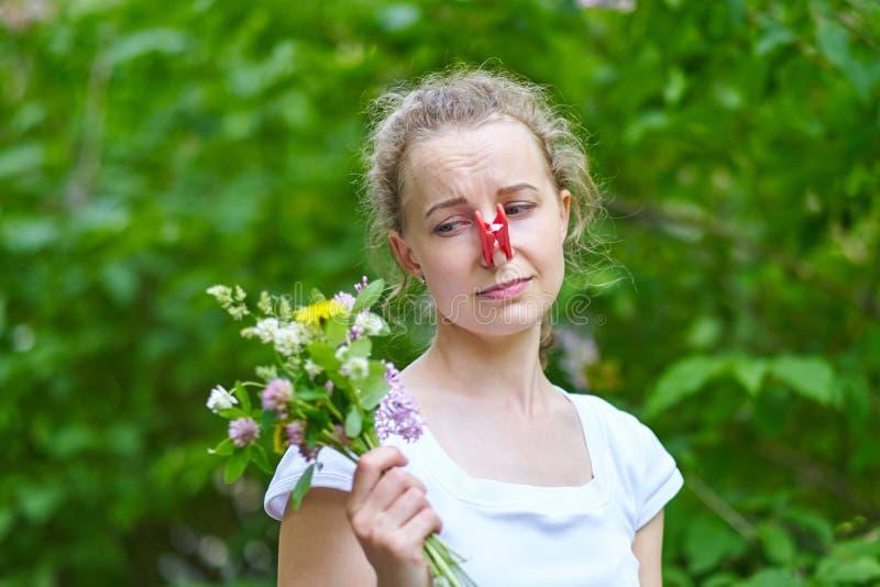 allergie La femme a serr? son nez avec une pince ? linge, pour pour ne pas ?ternuer du pollen des fleurs photo libre de droits