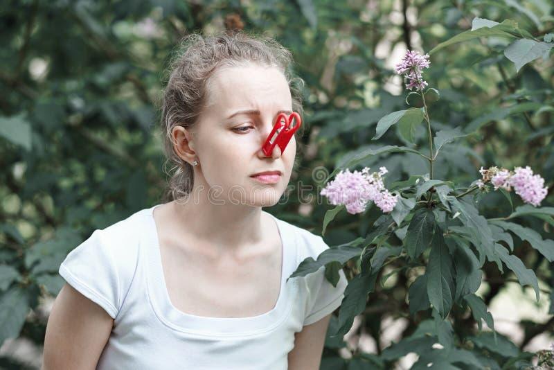 allergie La femme a serr? son nez avec la main, pour pour ne pas ?ternuer du pollen des fleurs Femme prot?geant son nez contre photo libre de droits