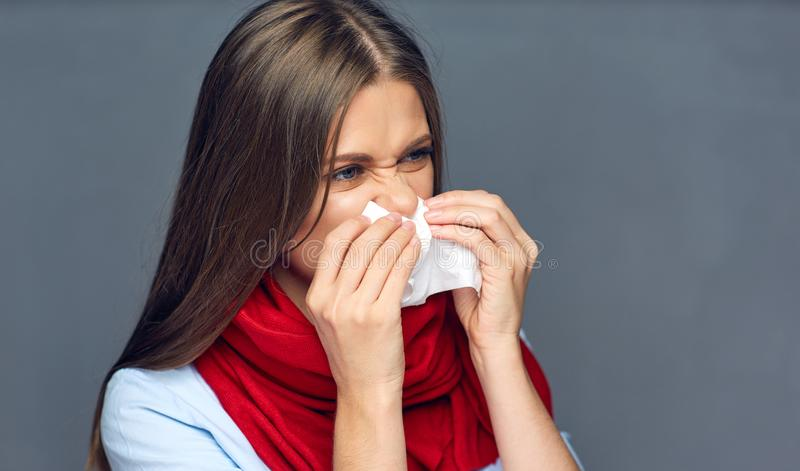 Allergies or flu sickness woman holding paper tissue. Isolated portrait on gray studio back stock image