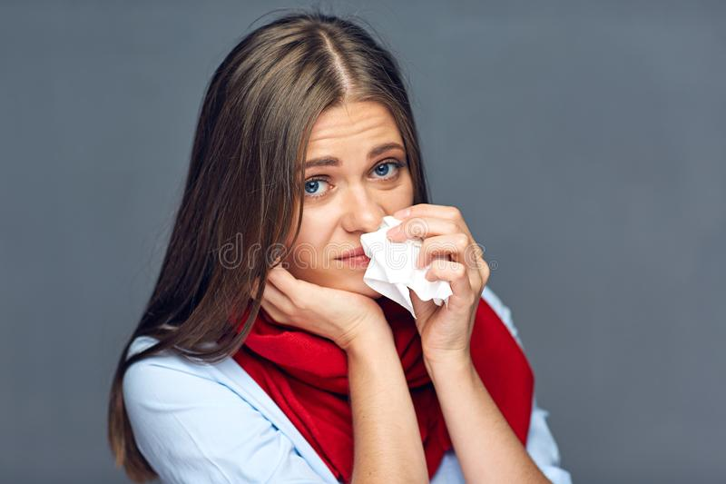 Allergies or flu sickness woman holding paper tissue. Isolated portrait on gray studio back royalty free stock images