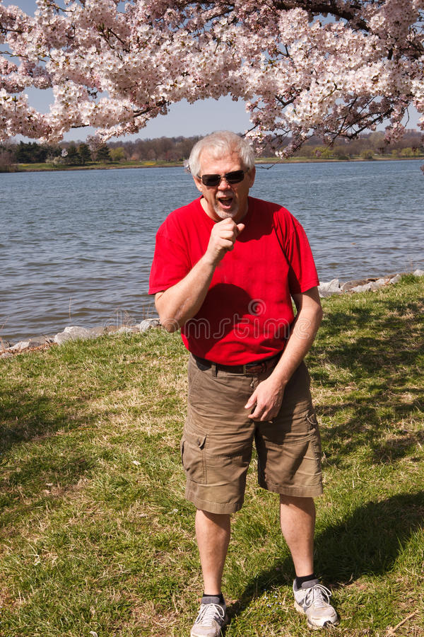 Spring Allergies. Senior man sneezes from the pollen of the trees blooming in the springtime in Washington, DC royalty free stock photos