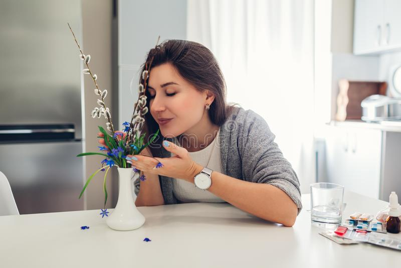 Allergin frigör Lycklig kvinna som luktar blommor efter återställning med piller bredvid på kök Säsongsbetonat allergibegrepp royaltyfria bilder