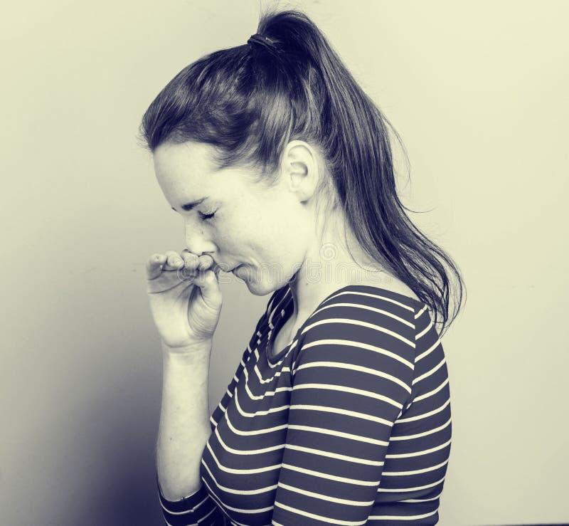 Allergin nyser skrapanäsan för den unga kvinnan i posera för hipster för modebandkläder tillfälligt på ljus bakgrund royaltyfria bilder