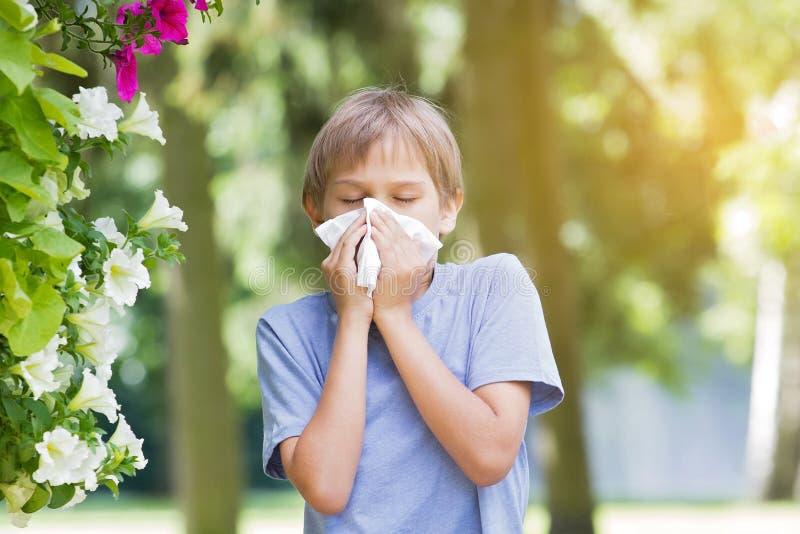 allergin Ungen blåser hans near blomstra blommor för näsan royaltyfri foto