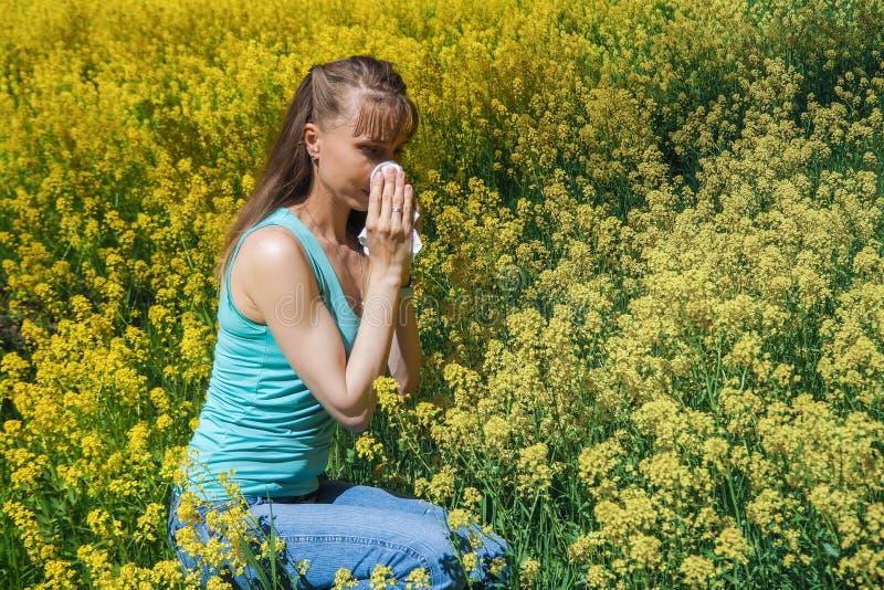 Allergiska reaktioner som fjädrar blommor, pollen, korsört Säsongsbetonad allergi Kvinnan som blåser hennes näsa i bakgrundsvår,  arkivfoto