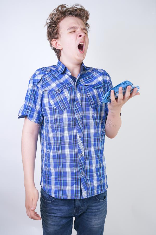 Allergy Boy Child with runny nose holding a handkerchief. Teenager is having bad health and standing on white studio background al. One. isolated stock photography