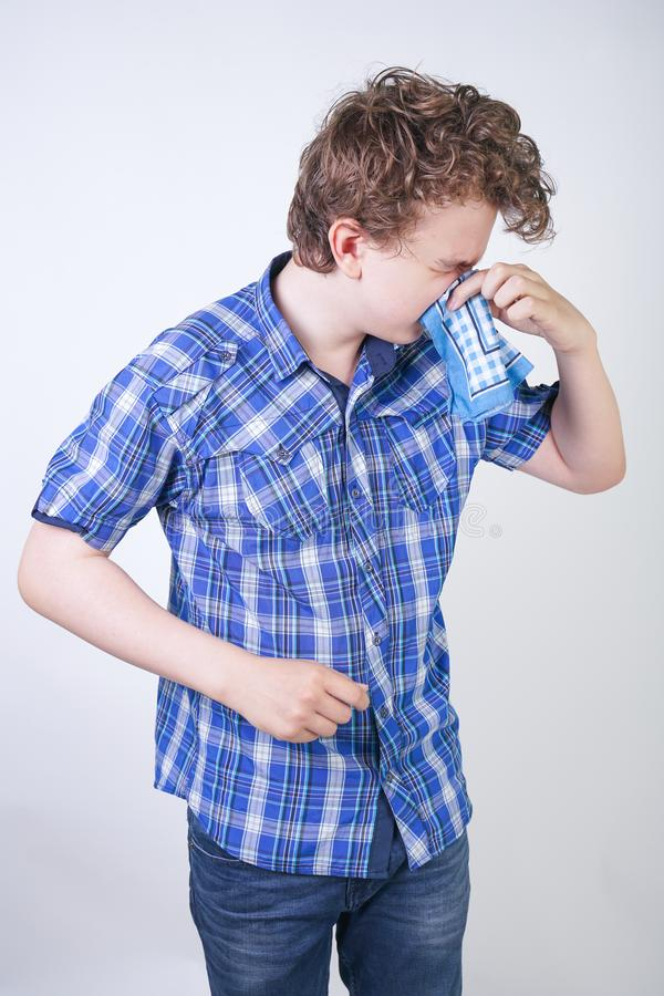 Allergy Boy Child with runny nose holding a handkerchief. Teenager is having bad health and standing on white studio background al. One. isolated stock image