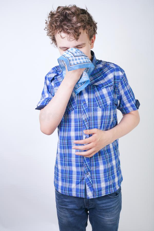 Allergy Boy Child with runny nose holding a handkerchief. Teenager is having bad health and standing on white studio background al. One. isolated stock photos