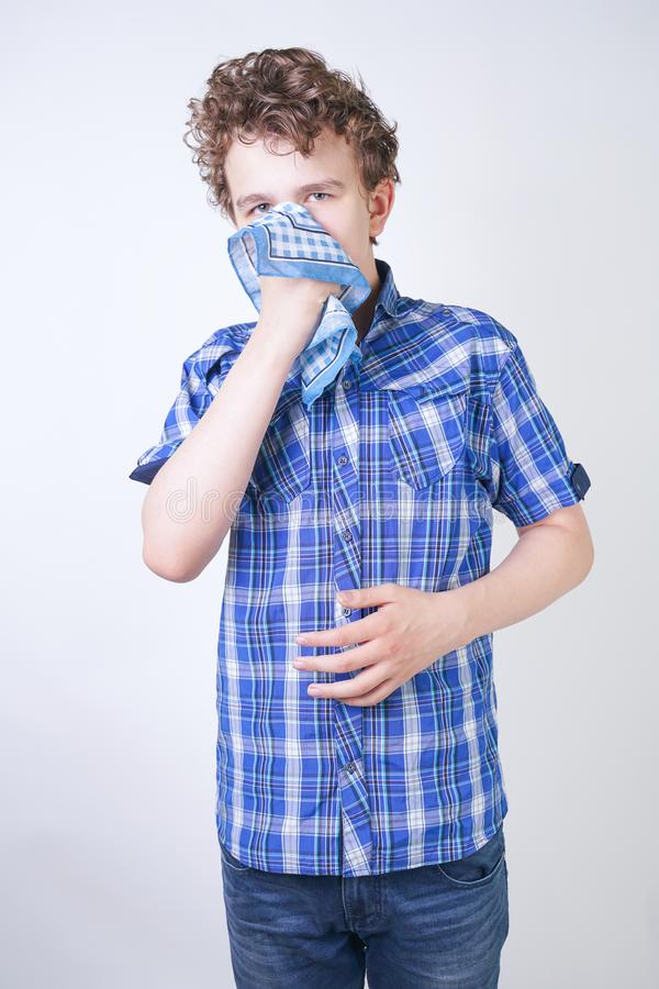 Allergy Boy Child with runny nose holding a handkerchief. Teenager is having bad health and standing on white studio background al. One. isolated royalty free stock images
