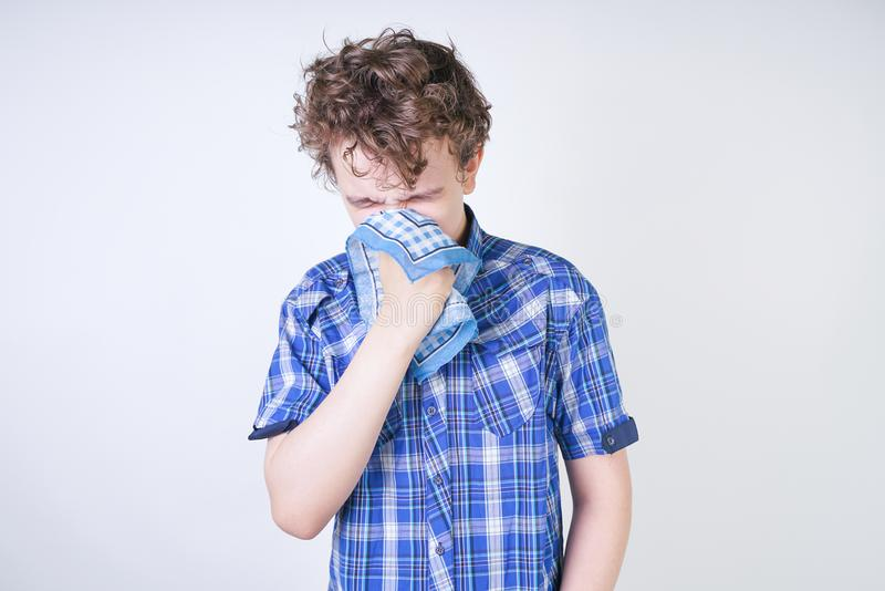 Allergy Boy Child with runny nose holding a handkerchief. Teenager is having bad health and standing on white studio background al. One. isolated royalty free stock image