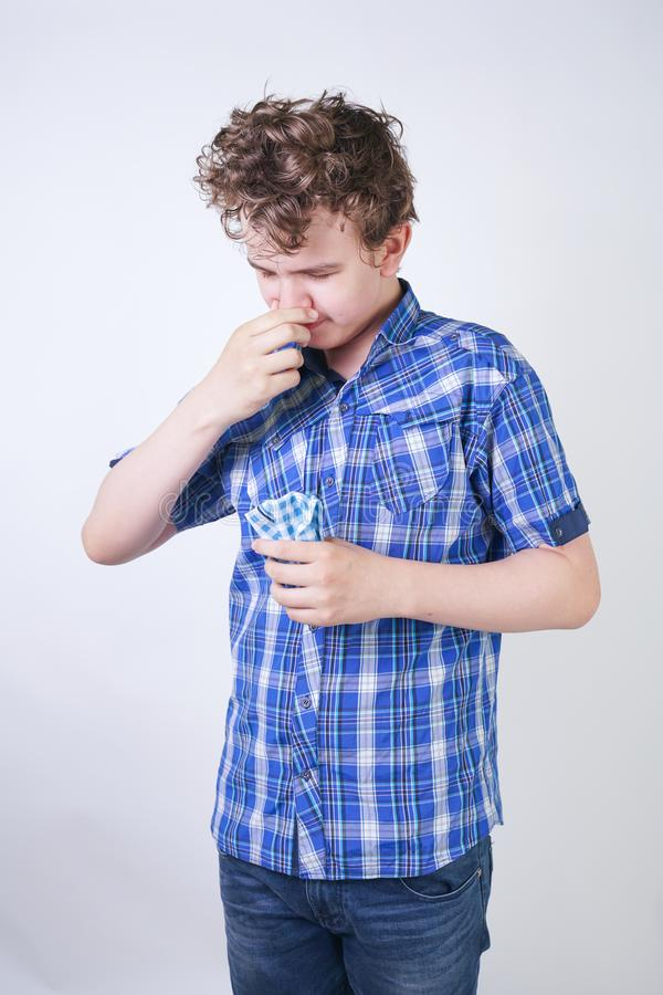 Allergy Boy Child with runny nose holding a handkerchief. Teenager is having bad health and standing on white studio background al. One. isolated stock photo