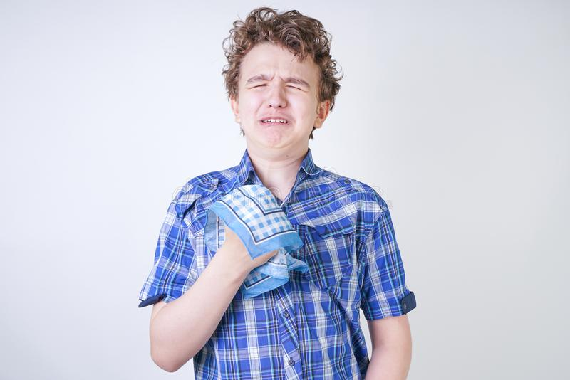 Allergy Boy Child with runny nose holding a handkerchief. Teenager is having bad health and standing on white studio background al. One. isolated stock images