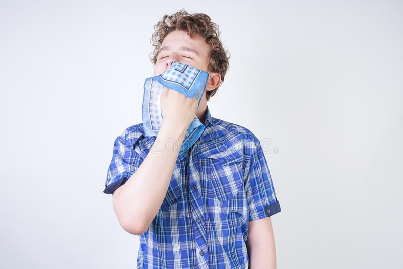 Allergy Boy Child with runny nose holding a handkerchief. Teenager is having bad health and standing on white studio background al. One. isolated royalty free stock photos