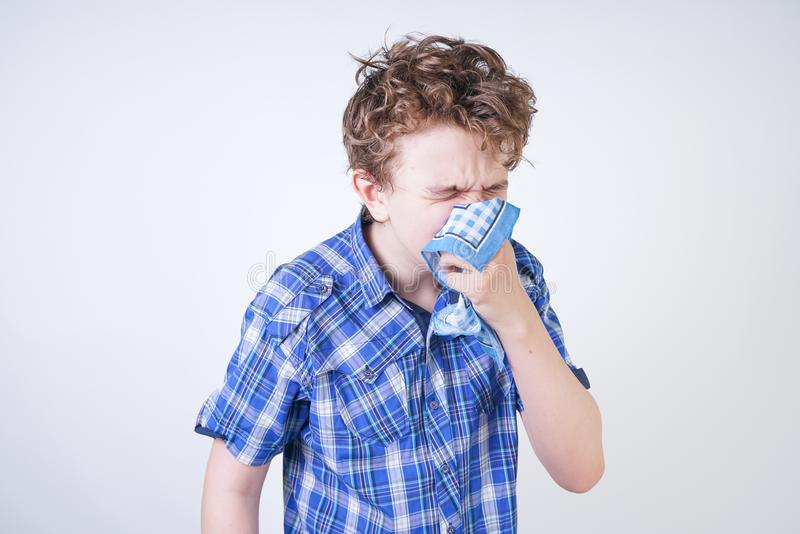 Allergy Boy Child with runny nose holding a handkerchief. Teenager is having bad health and standing on white studio background al. One. isolated royalty free stock photography