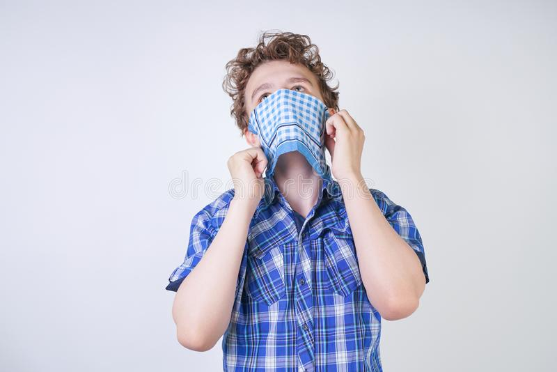 Allergy Boy Child with runny nose holding a handkerchief. Teenager is having bad health and standing on white studio background al. One. isolated royalty free stock photo