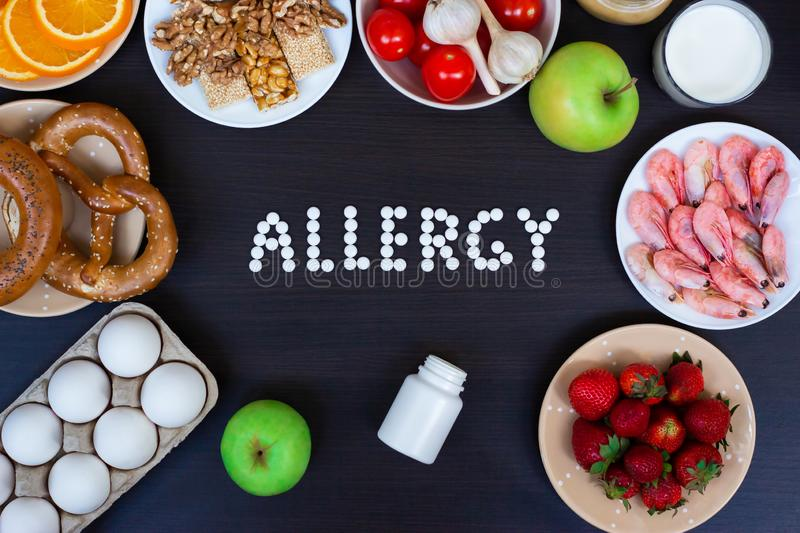 Allergy food as milk, oranges, tomatoes, garlic, shrimp, peanuts, eggs, apples, bread, strawberries on wooden table royalty free stock photography