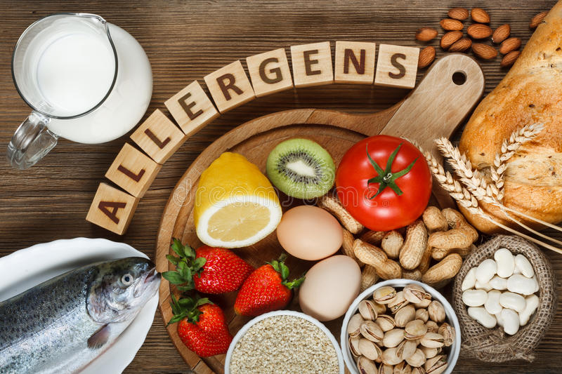 Allergy food. Concept.  as almonds, milk, pistachios, tomato, lemon, kiwi, trout, strawberry, bread, sesame seeds, eggs, peanuts and bean on wooden table royalty free stock photo