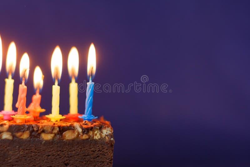 Alles Gute zum Geburtstag Brownie Cake mit Erdn?ssen, gesalzenem Karamell und bunten brennenden Kerzen auf Violet Background Kopi stockfoto