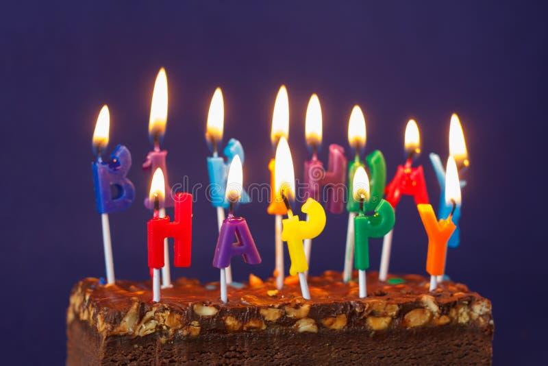 Alles Gute zum Geburtstag Brownie Cake mit Erdn?ssen, gesalzenem Karamell und bunten brennenden Kerzen auf Violet Background Kopi stockbilder