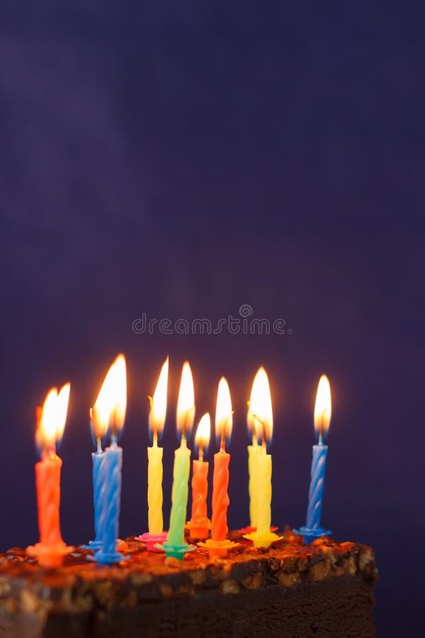 Alles Gute zum Geburtstag Brownie Cake mit Erdn?ssen, gesalzenem Karamell und bunten brennenden Kerzen auf Violet Background Kopi lizenzfreies stockfoto