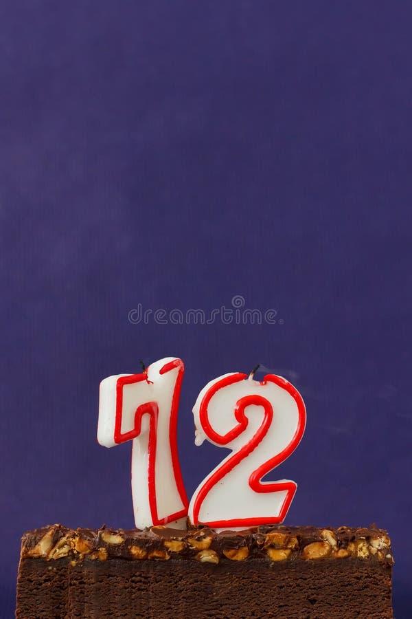 Alles Gute zum Geburtstag Brownie Cake mit Erdn?ssen, gesalzenem Karamell und bunten Unlighted Kerzen auf Violet Background Kopie stockfotos
