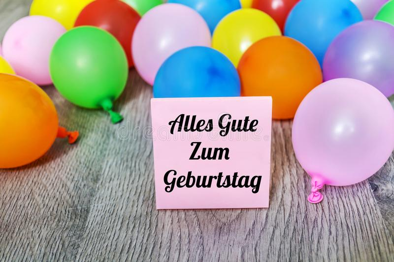 Alles Gute Zum Geburtstag Card with Balloons. Alles Gute Zum Geburtstag Message which means Happy Birthday with Colorful Balloon Frame on a Wooden Background stock photo