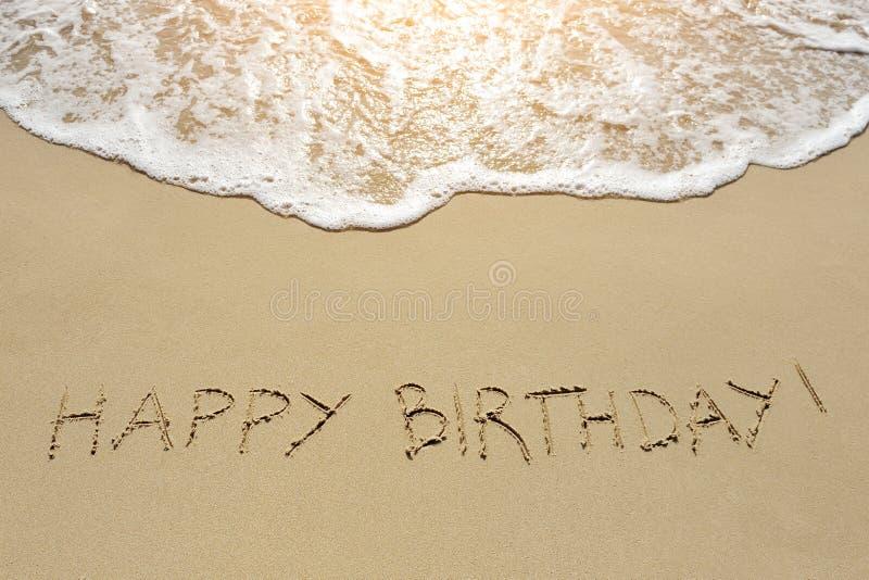 Alles Gute zum Geburtstag geschrieben auf Sandstrand lizenzfreie stockfotos