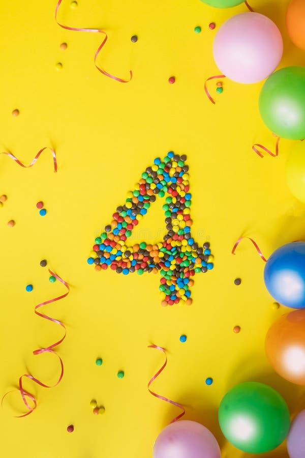 Alles Gute zum Geburtstag Nr. 4 machte von den Süßigkeiten mit bunten Ballonen auf gelbem Hintergrund lizenzfreie stockfotografie