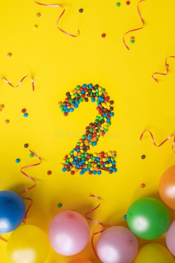 Alles Gute zum Geburtstag Nr. 2 machte von den Süßigkeiten mit bunten Ballonen auf gelbem Hintergrund stockfotografie