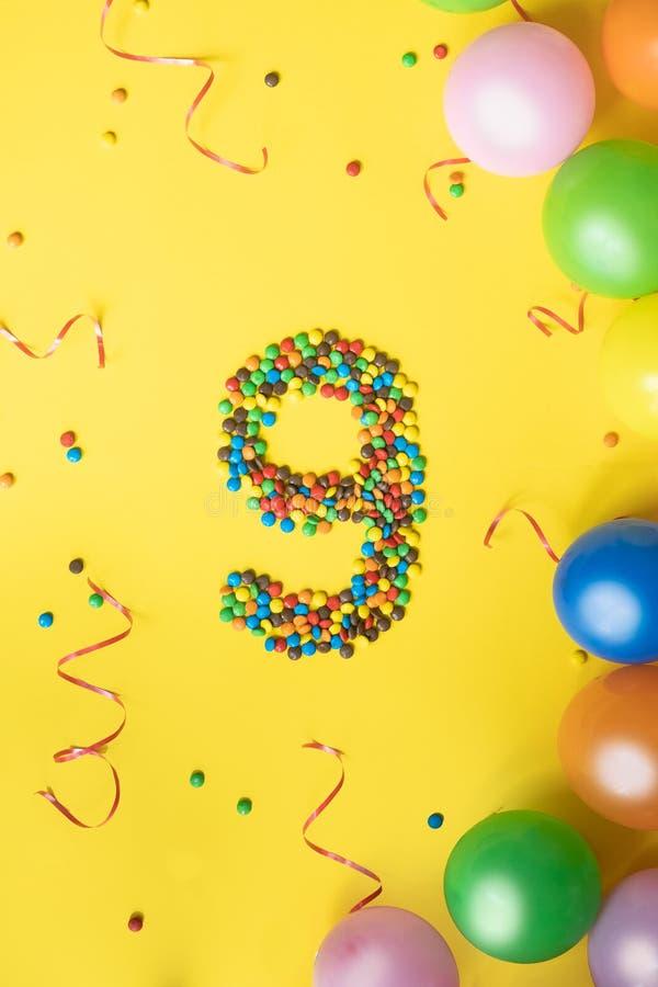 Alles Gute zum Geburtstag Nr. 9 machte von den Süßigkeiten mit bunten Ballonen auf gelbem Hintergrund stockfoto