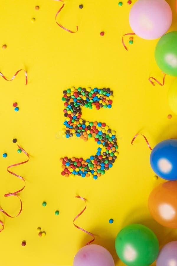 Alles Gute zum Geburtstag Nr. 5 machte von den Süßigkeiten mit bunten Ballonen auf gelbem Hintergrund lizenzfreie stockfotos