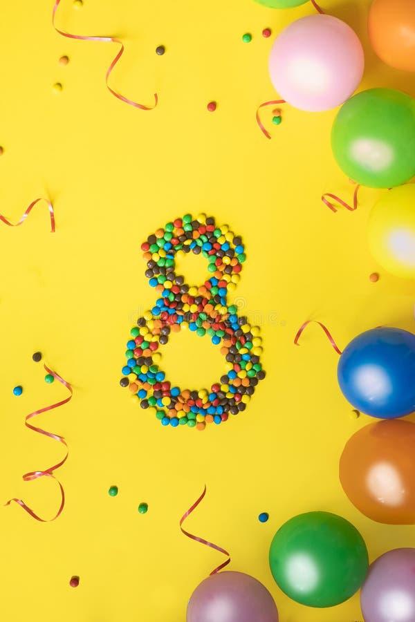Alles Gute zum Geburtstag Nr. 8 machte von den Süßigkeiten mit bunten Ballonen auf gelbem Hintergrund stockfotos