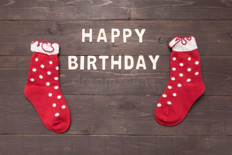 Alles Gute zum Geburtstag und Socken sind auf hölzernem Hintergrund stockfoto