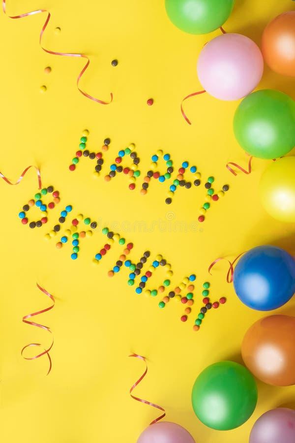 Alles- Gute zum Geburtstagbuchstaben von den Süßigkeiten Enthält transparente Nachrichten Bunte Ballone und Süßigkeiten auf gelbe lizenzfreie stockfotografie