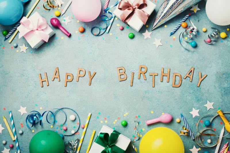 Alles- Gute zum Geburtstagfahne Bunte Feiertagsversorgungen auf blauer Weinlesetischplatteansicht flache Lageart lizenzfreie stockfotos