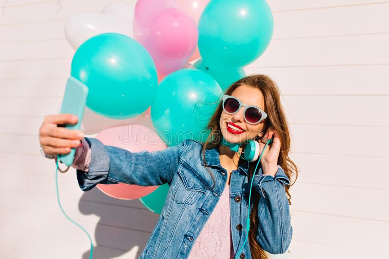 Alles- Gute zum Geburtstagmädchen mit den Ballonen, die selfie während hörende Musik machen und Partei genießen Bezaubernde brune lizenzfreie stockfotografie