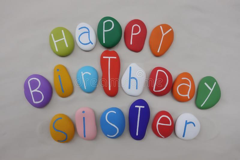 Alles- Gute zum Geburtstagschwester mit farbigen Steinen über weißem Sand stockfoto